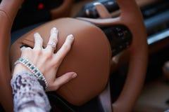 Vrouw die gele sportwagen met het stuurwiel van de handgreep drijven stock fotografie