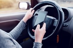 Vrouw die gelijktijdig auto drijven en tekstbericht lezen royalty-vrije stock afbeelding
