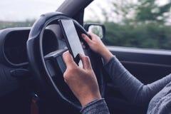 Vrouw die gelijktijdig auto drijven en tekstbericht typen royalty-vrije stock fotografie