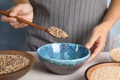 Vrouw die gemengde quinoa zaden gieten in kom bij lijst royalty-vrije stock foto's