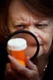 Vrouw die geneeskundefles onderzoekt stock foto's