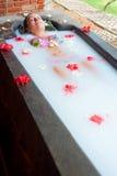 Vrouw die genoegen in melkbad neemt Stock Afbeeldingen