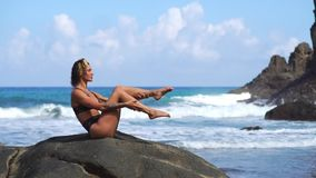Vrouw die geschiktheid op het strand met vulkanisch zwart zand in een zwempakzitting doen op een rots rond de bergen van lava stock videobeelden