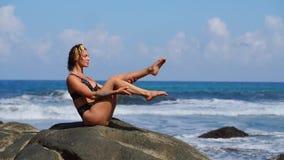 Vrouw die geschiktheid op het strand met vulkanisch zwart zand in een zwempakzitting doen op een rots rond de bergen van lava stock footage