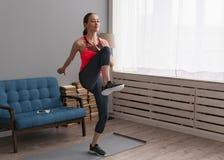 Vrouw die geschiktheid thuis en het lopen hoge knieën doen die opleiden Royalty-vrije Stock Afbeelding