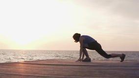 Vrouw die geschiktheidstraining doen bij zonsondergang door het overzees stock videobeelden