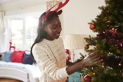 Vrouw die Geweitakken dragen die Decoratie op Kerstboom thuis hangen royalty-vrije stock afbeelding
