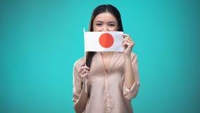 Vrouw die gezicht behandelen met de vlag van Japan, lerend taal, onderwijs en reis stock videobeelden
