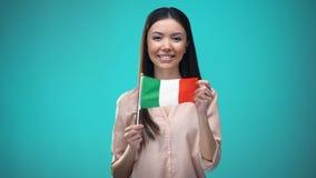 Vrouw die gezicht behandelen met Italiaanse vlag, lerend taal, onderwijs en reis stock videobeelden