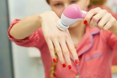 Vrouw die gezichts reinigende borstel houden royalty-vrije stock afbeeldingen