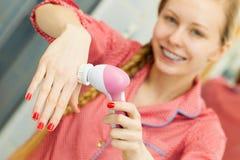 Vrouw die gezichts reinigende borstel houden stock afbeeldingen