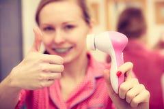 Vrouw die gezichts reinigende borstel houden stock foto's