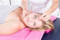 Vrouw die gezichtsacupunctuurbehandeling op jong aantrekkelijk meisje ontvangen royalty-vrije stock afbeelding