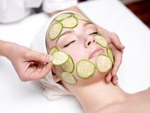 Vrouw die gezichtsmasker van komkommer ontvangt Stock Afbeelding