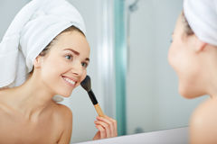 Vrouw die gezichtspoeder in de badkamers toepassen royalty-vrije stock foto