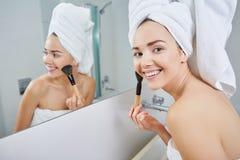 Vrouw die gezichtspoeder in de badkamers toepassen stock afbeeldingen