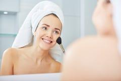 Vrouw die gezichtspoeder in de badkamers toepassen royalty-vrije stock foto's