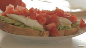 Vrouw die gezond ontbijt met avocado op geroosterde brood, eieren en tomaat voorbereiden stock footage