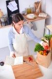 Vrouw die gezonde voedsel status maken glimlachend in keuken Stock Afbeeldingen