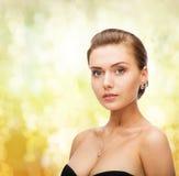 Vrouw die glanzende diamantoorringen en tegenhanger dragen royalty-vrije stock foto's