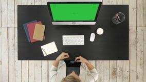 Vrouw die glazen aanzetten terwijl het gebruiken van computer De groene Vertoning van het het Schermprototype stock footage
