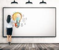 Vrouw die gloeilamp trekt op whiteboard royalty-vrije stock afbeelding