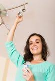 Vrouw die gloeilamp verandert Stock Fotografie