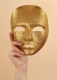 Vrouw die gouden masker houdt royalty-vrije stock afbeeldingen