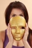 Vrouw die gouden masker houdt royalty-vrije stock fotografie