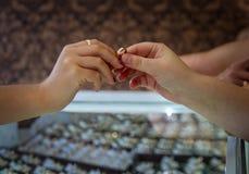 Vrouw die gouden ring in juwelenopslag kopen Stock Foto