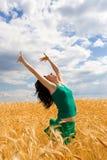 Vrouw die in gouden tarwe springt Stock Afbeeldingen