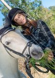 Vrouw die gras geven aan paard royalty-vrije stock afbeelding