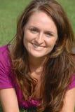 Vrouw die in gras het glimlachen legt. stock foto's