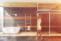 Vrouw die in grijze badkamers met ton en douche lopen stock afbeelding