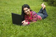 Vrouw die in groen gras legt en aan laptop werkt Royalty-vrije Stock Fotografie