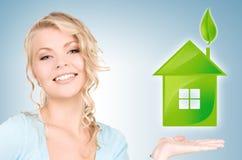 Vrouw die groen huis in haar handen houden Stock Foto's
