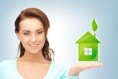Vrouw die groen huis in haar handen houden Royalty-vrije Stock Afbeelding