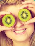 Vrouw die groen kiwifruit zoals oogglazen houden Royalty-vrije Stock Afbeeldingen