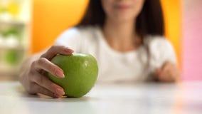 Vrouw die groene appel, gezonde snack, organisch fruit, vegetarische levensstijl houden stock afbeeldingen