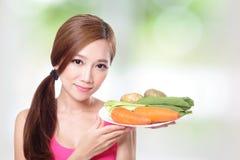 Vrouw die groene groenten en wortelen houden Stock Afbeelding