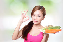 Vrouw die groene groenten en wortelen houden Stock Foto's