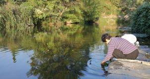 Vrouw die groene groenten wassen door de pool in wuyuan provincie, rgb adobe stock fotografie