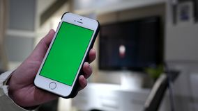 Vrouw die groene het schermiphone met onscherpe woonkamer houden stock video