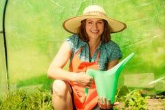 Vrouw die groene tomatenplanten in serre water geven Stock Foto's