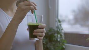 Vrouw die groene verse smoothie van in de keuken drinken stock videobeelden