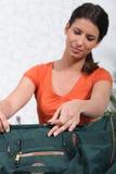 Vrouw die groene zak inpakt Stock Afbeeldingen