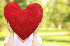 Vrouw die groot rood hart houdt vóór haar gezicht stock foto