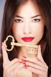 Vrouw die grote oude sleutel houdt Royalty-vrije Stock Foto's