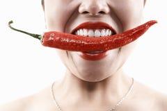 Vrouw die grote rode Spaanse peper in mond houdt Stock Afbeelding