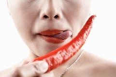 Vrouw die grote rode Spaanse peper proeft Stock Foto's